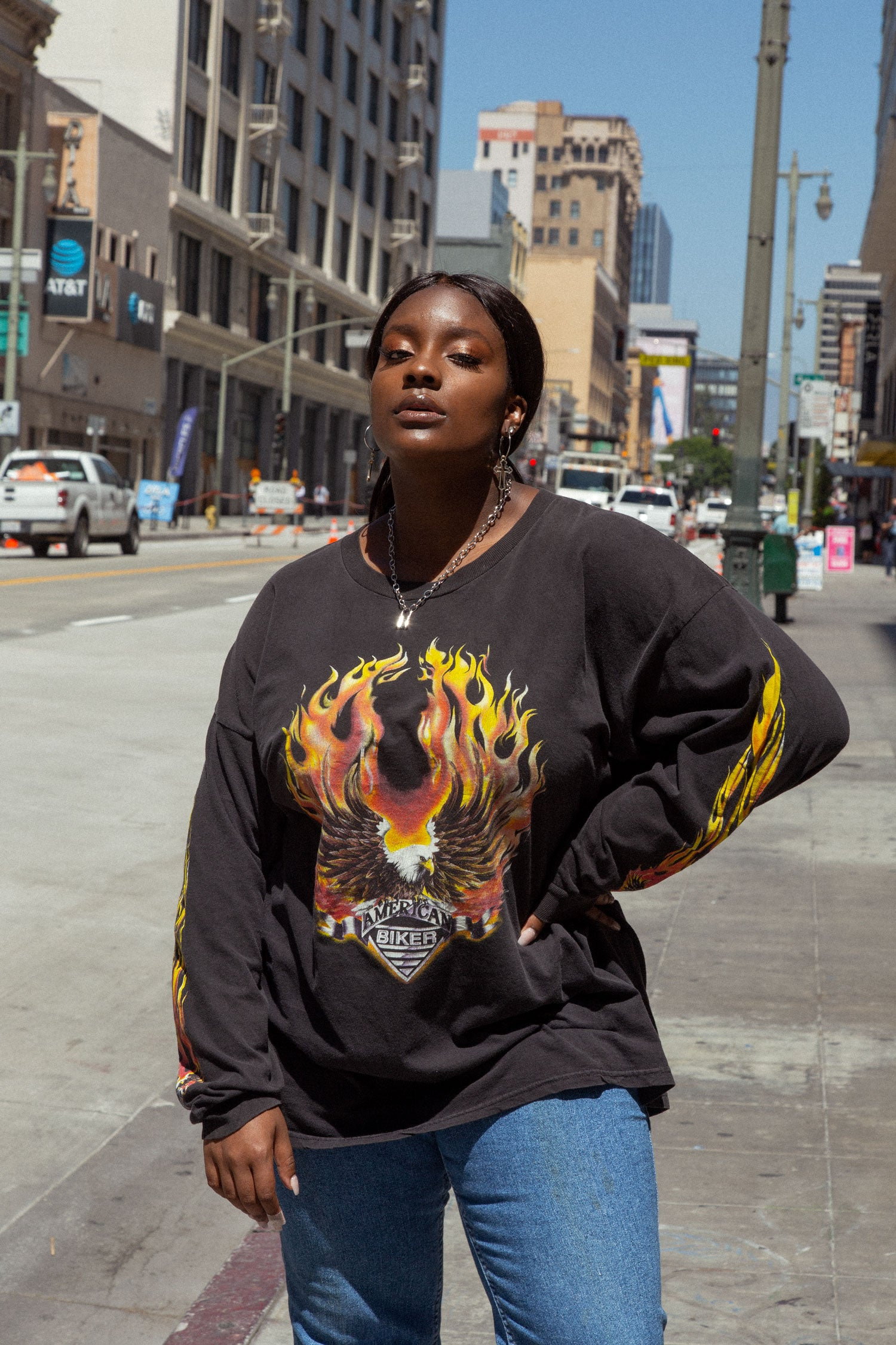 Plus size female model standing in city, wearing vintage 90s flame t shirt.