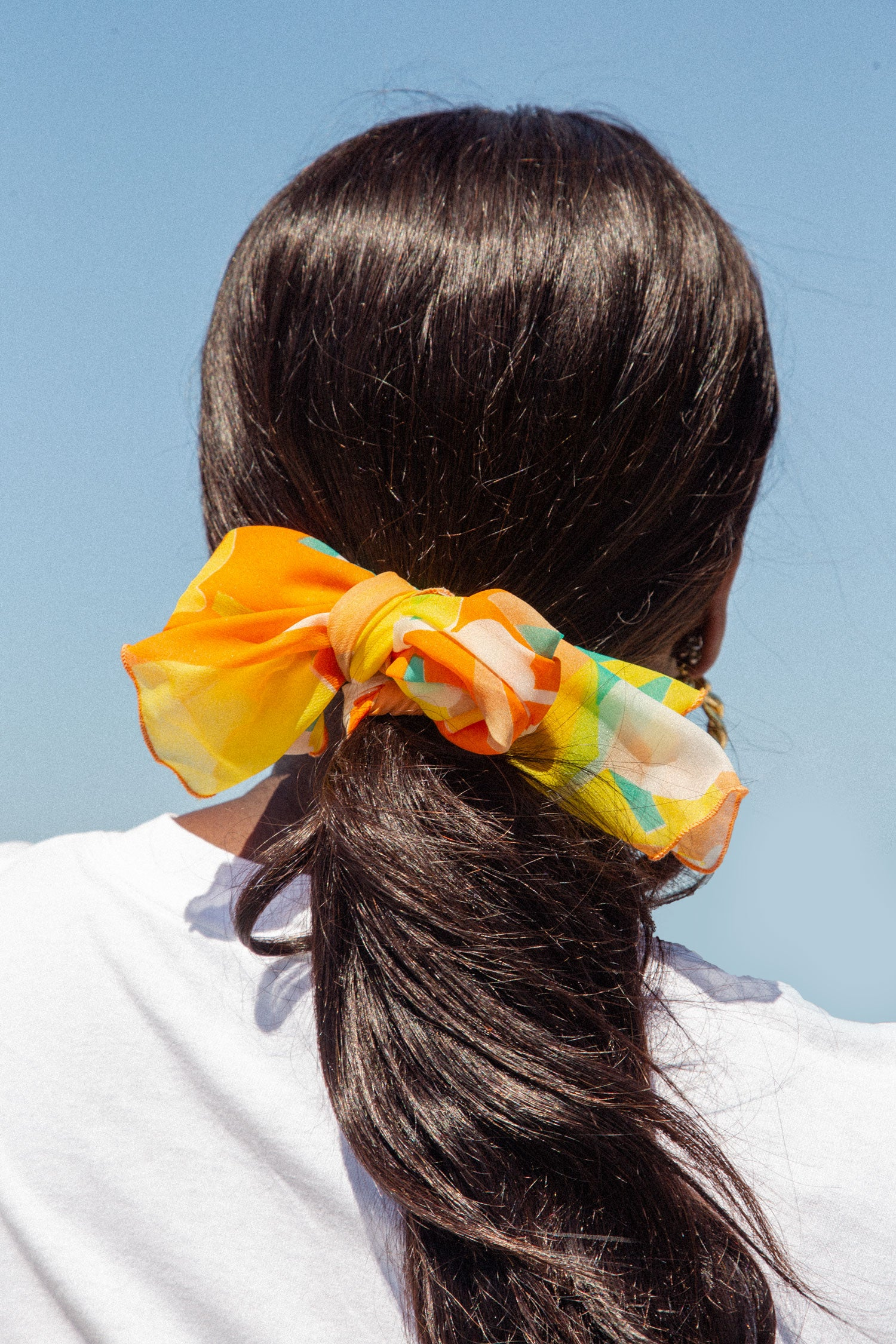 Pony tail with vintage orange silk scarf tied around it.