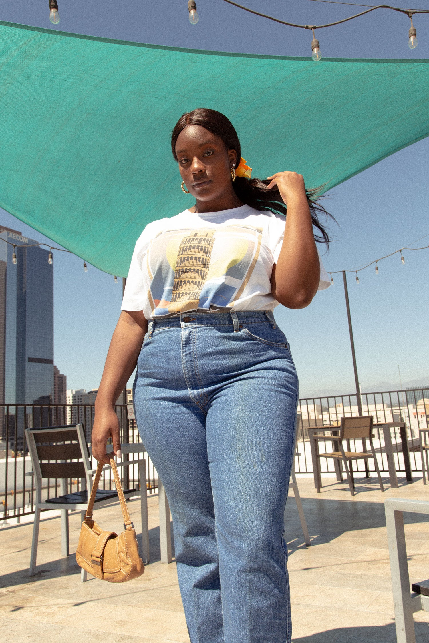 Plus size female model standing on rooftop in downtown Los Angeles.  Wearing vintage Leaning Tower of Pisa t shirt, and high waisted Levi's.