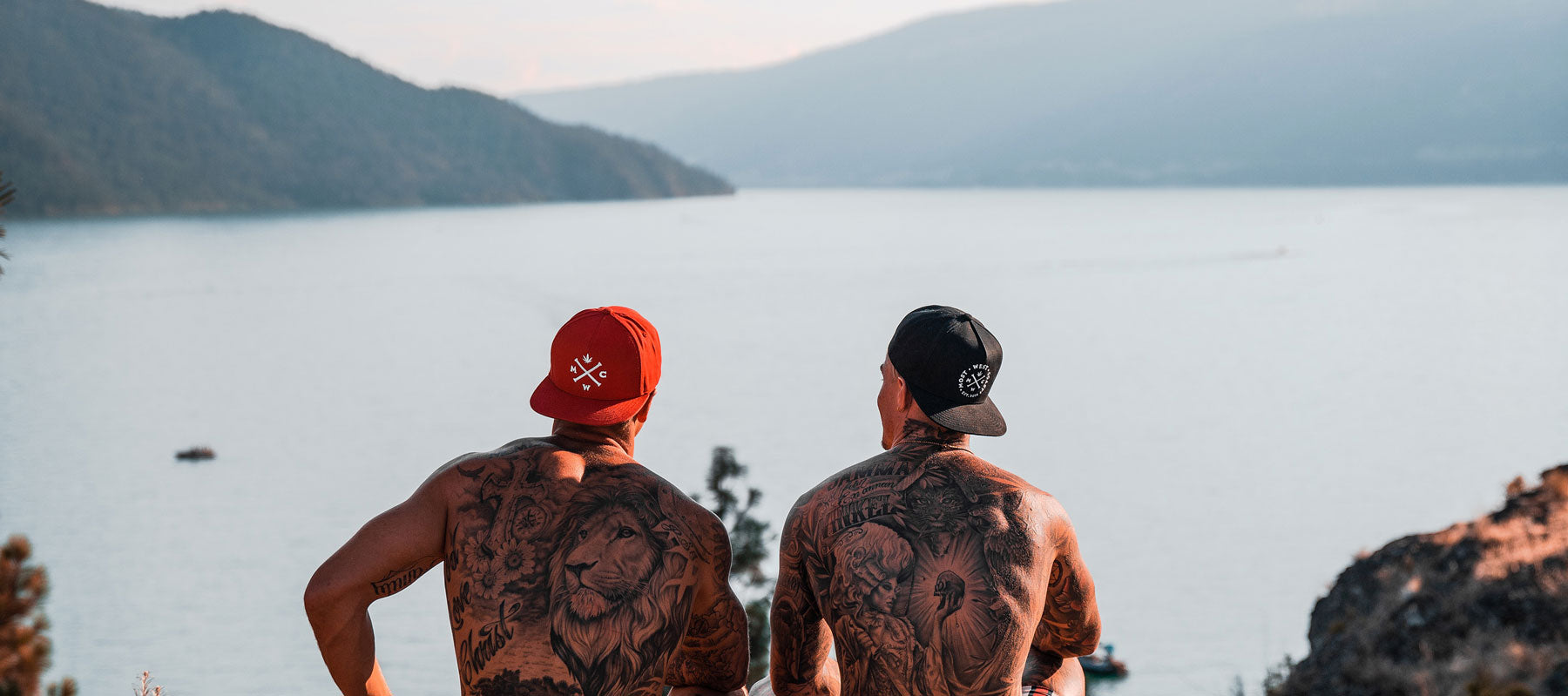 2 guys hanging out on the coast, wearing Most West Coast Snapback hats. One hat is red, the other hat is black.
