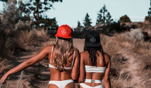 2 women hanging out on the coast wearing Most West Coast Apparel Snapback hats. 1 hat is red, the other is black.