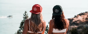 2 women hanging out on the coast wearing Most West Coast Apparel Snapback style hats. 1 hat is red, the other is black.