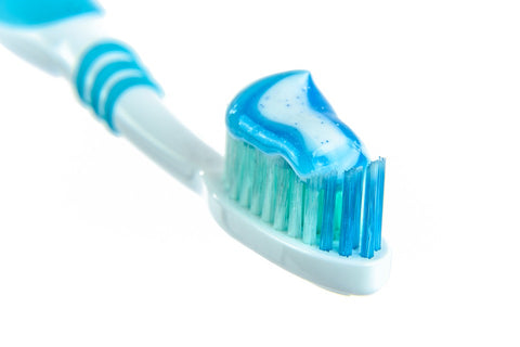 blue paste on the white and blue tooth brush