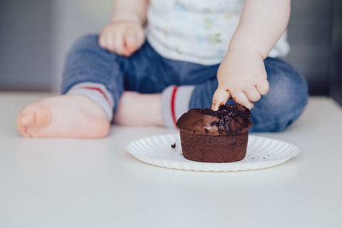 a baby putting finger into the chocolate muffin
