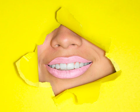a part of female face showing up through the yellow paper curtain