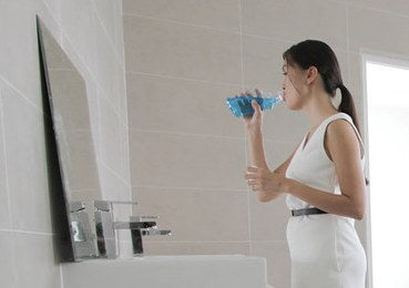 a woman rinsing her mouth