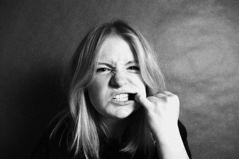 a blonde girl showing her teeth issue