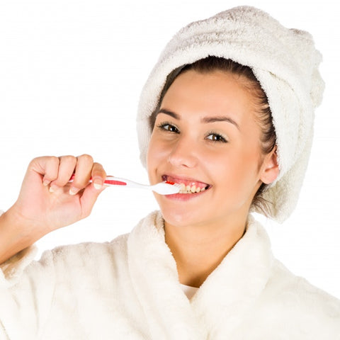 a woman with a towel on her head brushing teeth