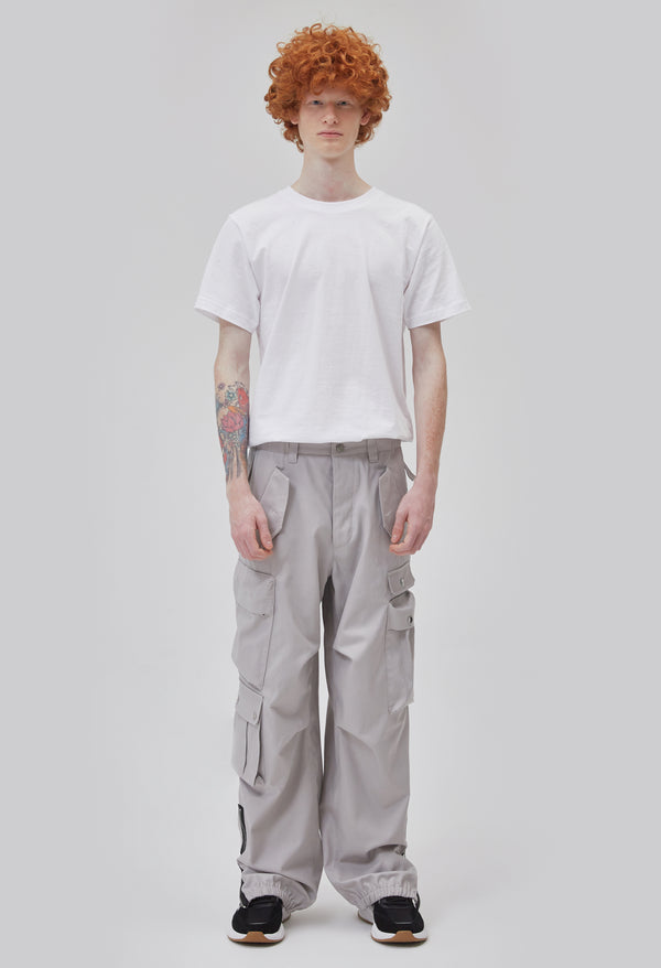 ZENSAI Loose Light Grey Cargo Ankle Zip Pant with Multiple Pockets and Ankle Zippers Front View on Male Model