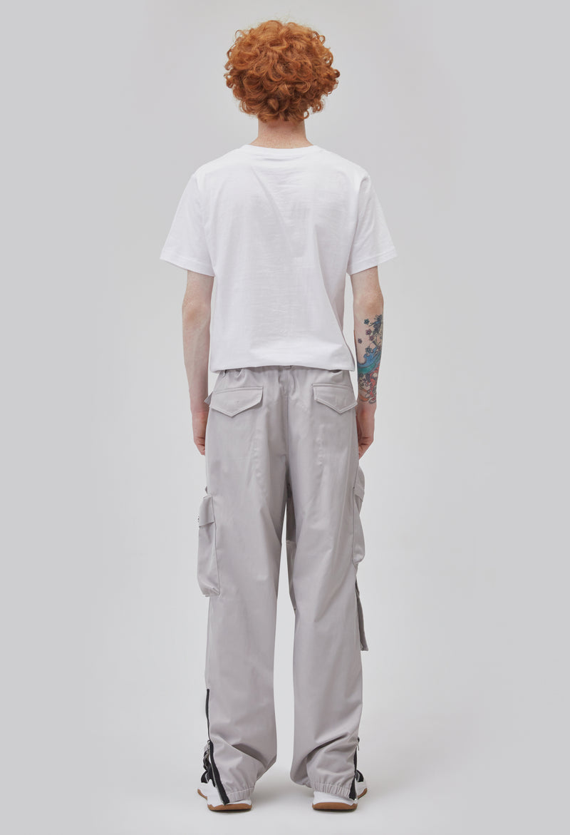 ZENSAI Loose Light Grey Cargo Ankle Zip Pant with Multiple Pockets and Ankle Zippers Back View on Male Model