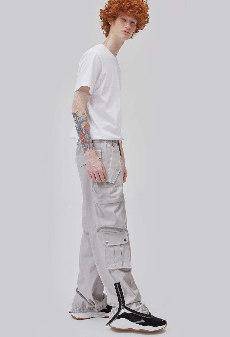ZENSAI Loose Light Grey Cargo Ankle Zip Pant with Multiple Pockets and Ankle Zippers Dynamic Side View on Male Model