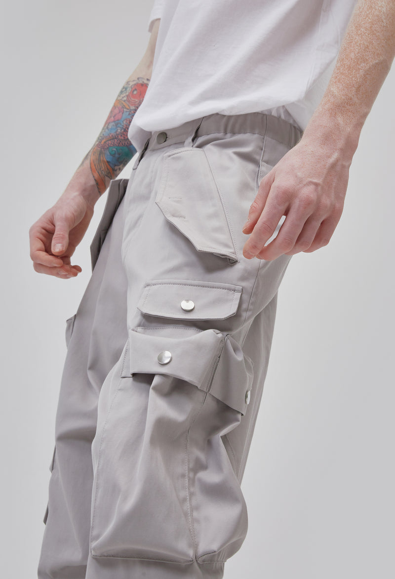 ZENSAI Loose Light Grey Cargo Ankle Zip Pant with Multiple Pockets and Ankle Zippers Side Thigh Close Up View on Male Model