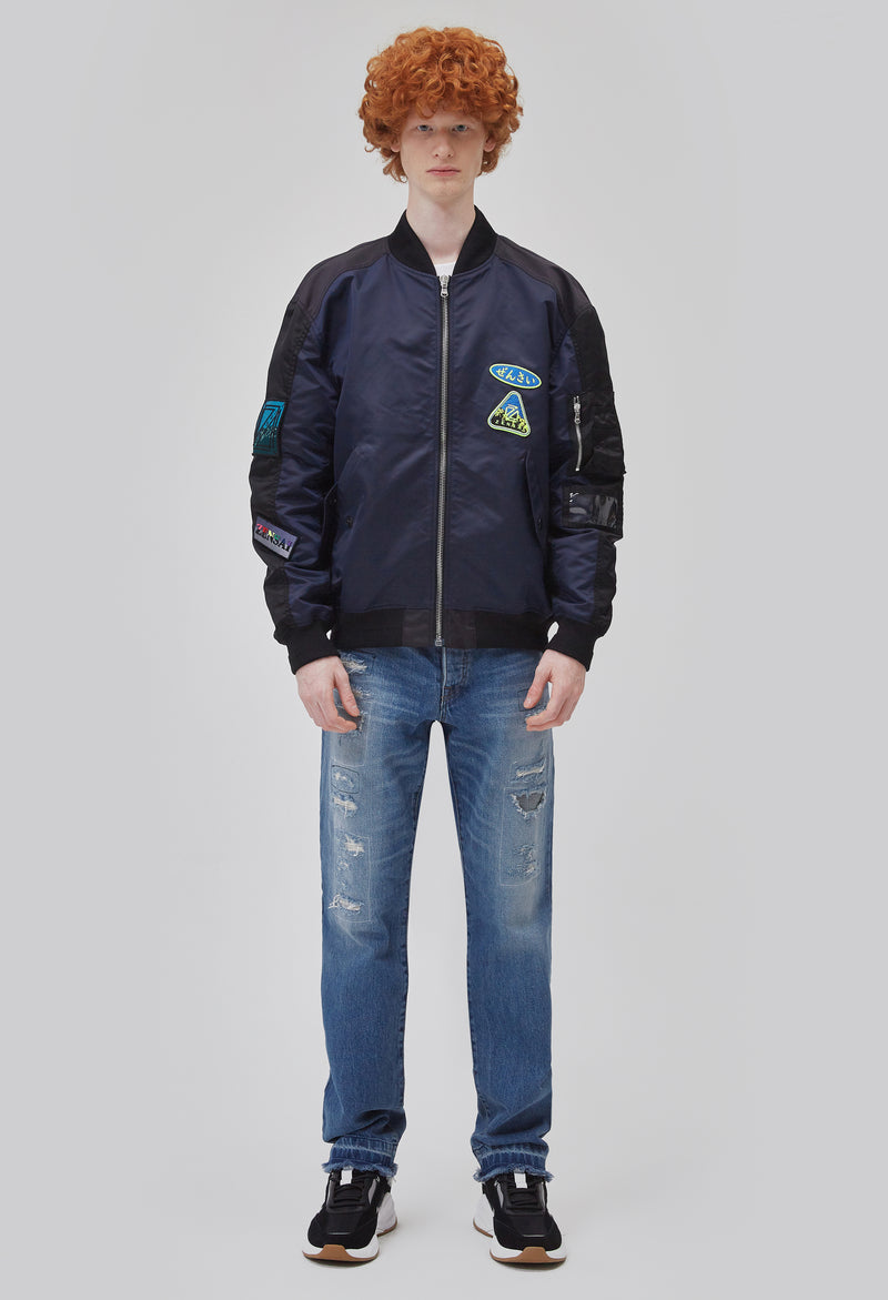 ZENSAI Black and Blue Patched Bomber Jacket Zipped Front View on Male Model