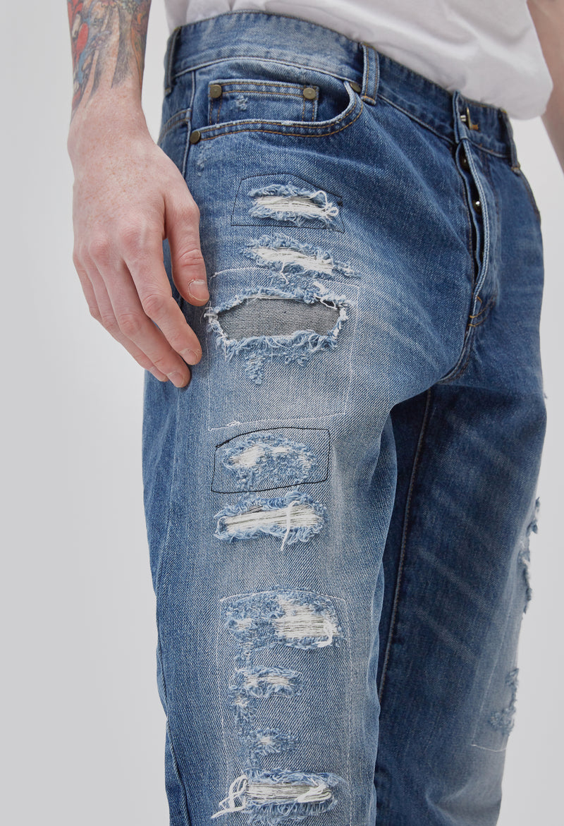 ZENSAI Distressed Patched Blue Jeans Thigh Details 3/4 View on Male Model