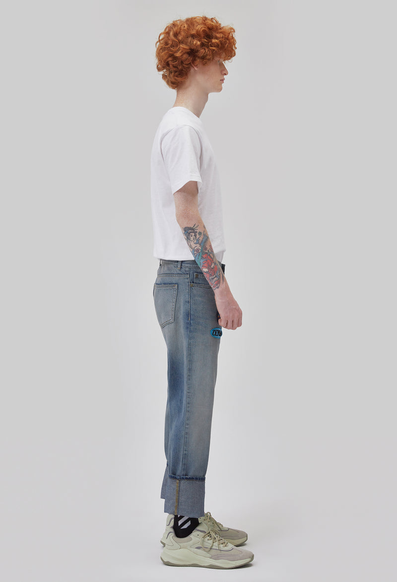 ZENSAI Faded Blue Logo Patch Jeans with Embroidered Details Side View on Male Model