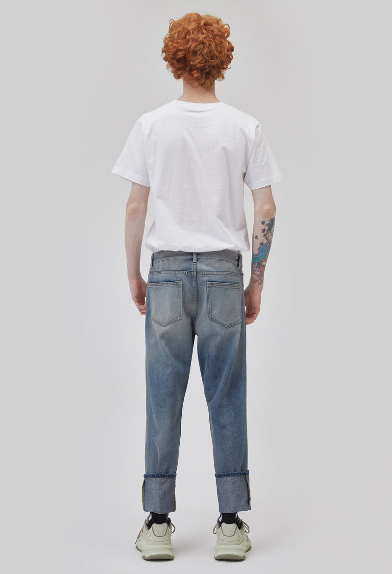 ZENSAI Faded Blue Logo Patch Jeans with Embroidered Details Back View on Male Model