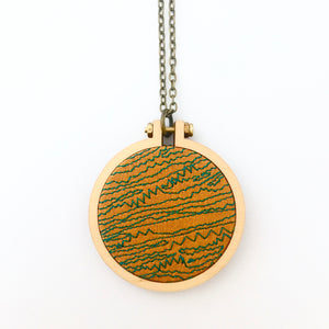 machine embroidered pendant . mustard lines .