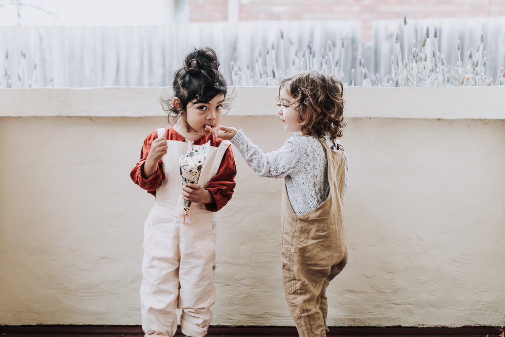 Children eating popcorn from beeswax wrap cones made with organic Australian beeswax and certified organic cotton