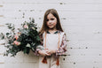 Girl holding bouquet of proteas and eucalyptus with stems wrapped in a wintering beeswax wrap