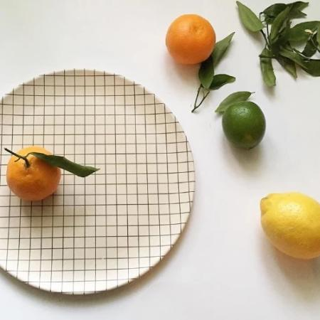 Grid Pattern Bamboo Dinner Plate with citrus fruits.