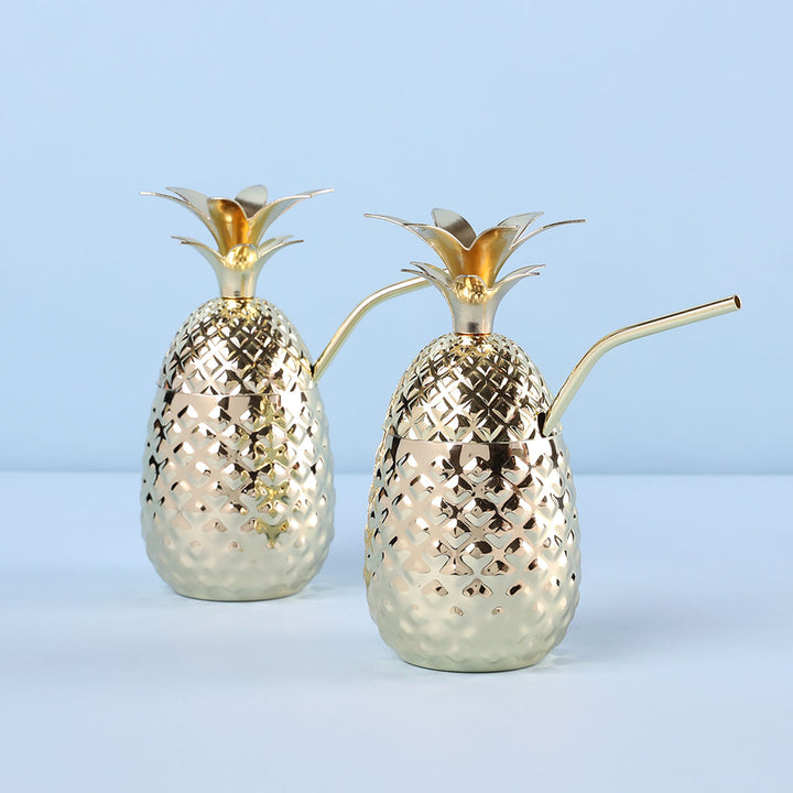 Gold pineapple shaped drink tumbler with straw.