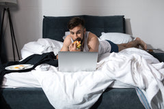 Guy eating in bed