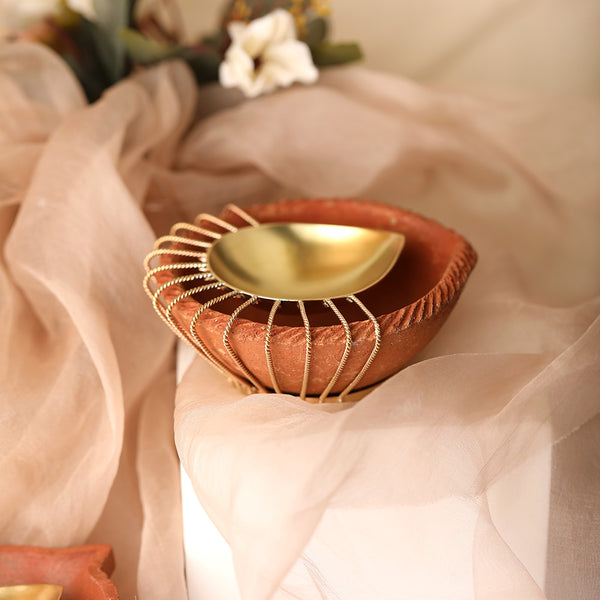 Gold plated metal diya encompassed by earthy terracotta with ornate wire detailing