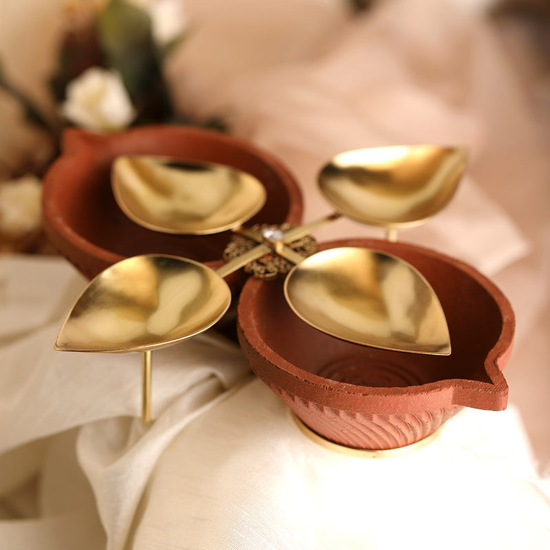 Decorative open gold plated metal diya encompassed by earthy terracotta with filigree embellishment