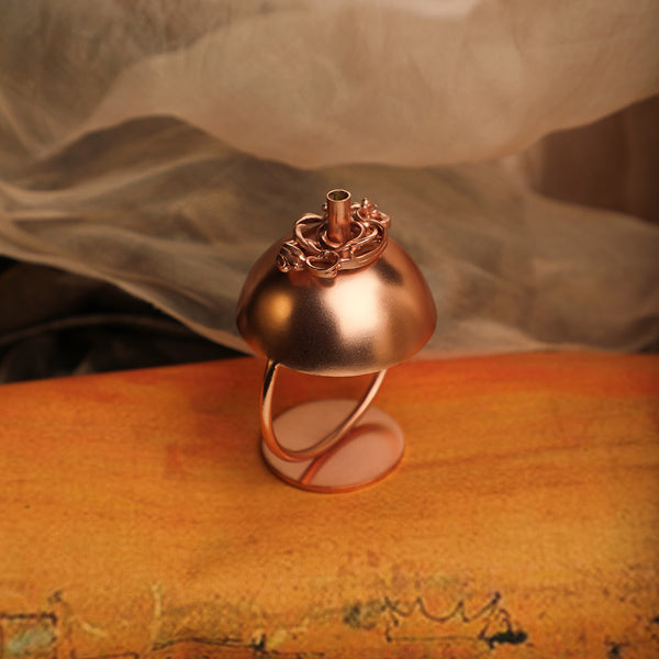 Copper plated spherical incense stick holder with circular base and ornate entwined detailing