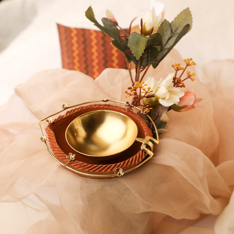 Gold plated metal diya encompassed by earthy terracotta with intricate floral border