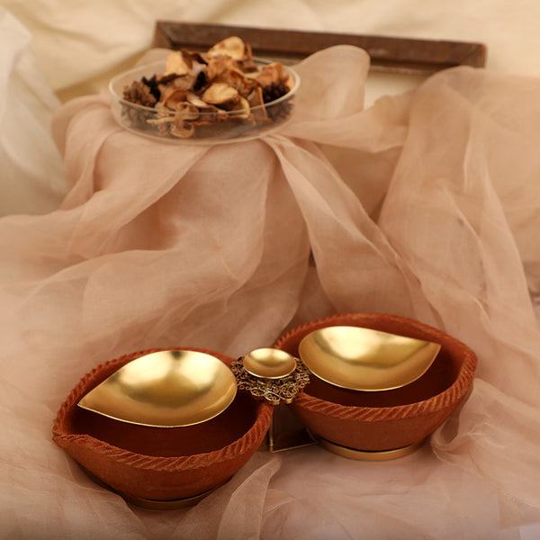 Gold plated metal diya duo encompassed by earthy terracotta with filigree detailing