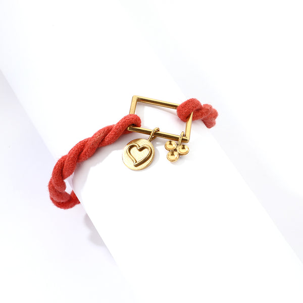 Gold plated square motif and charms with a twisted red cord