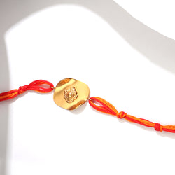GOLD TONED RAKHI WITH FLORAL MOTIF