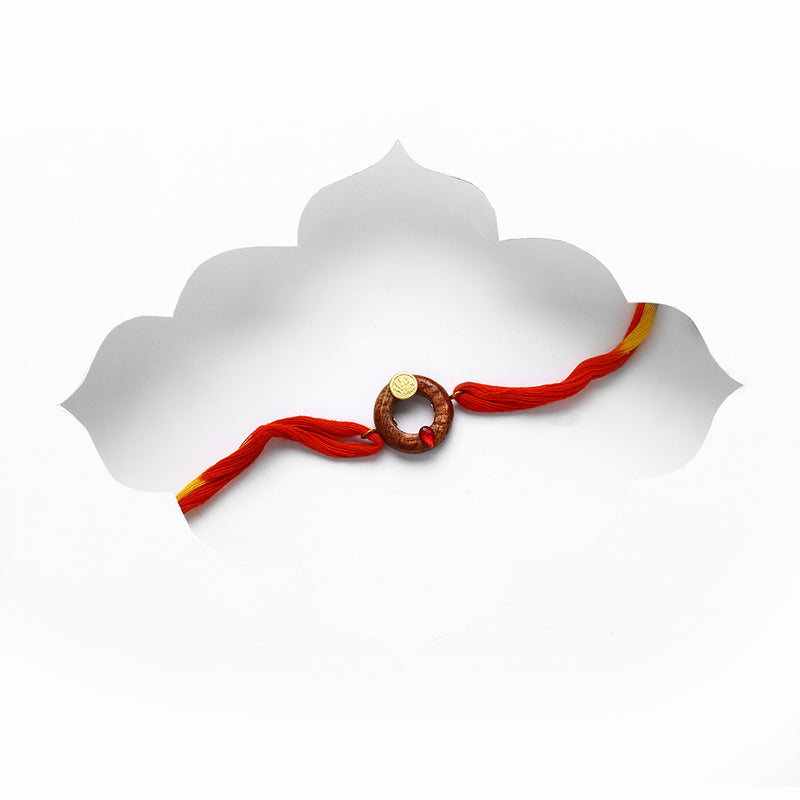 circular-wooden-rakhi-with-ganesh-coin-&-red-crystal-on-red-threads