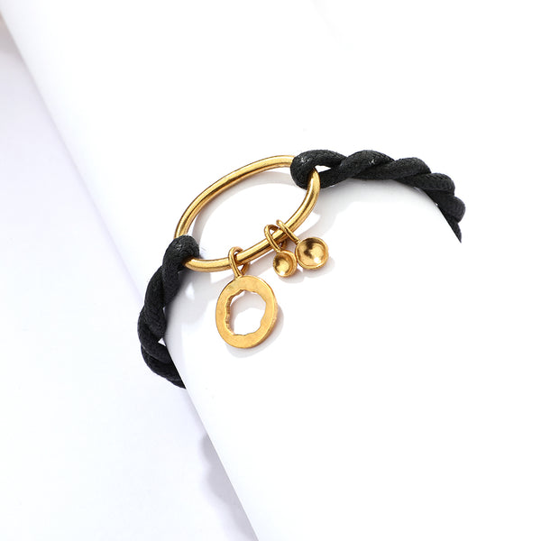 Gold plated oval motif and charms with a twisted black cord