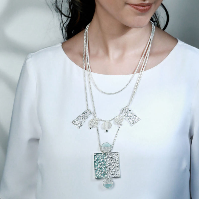 SILVER TONED LAYERED CHARMS NECKLACE WITH CYAN ACRYLIC DOTTED BLOCK PENDANT