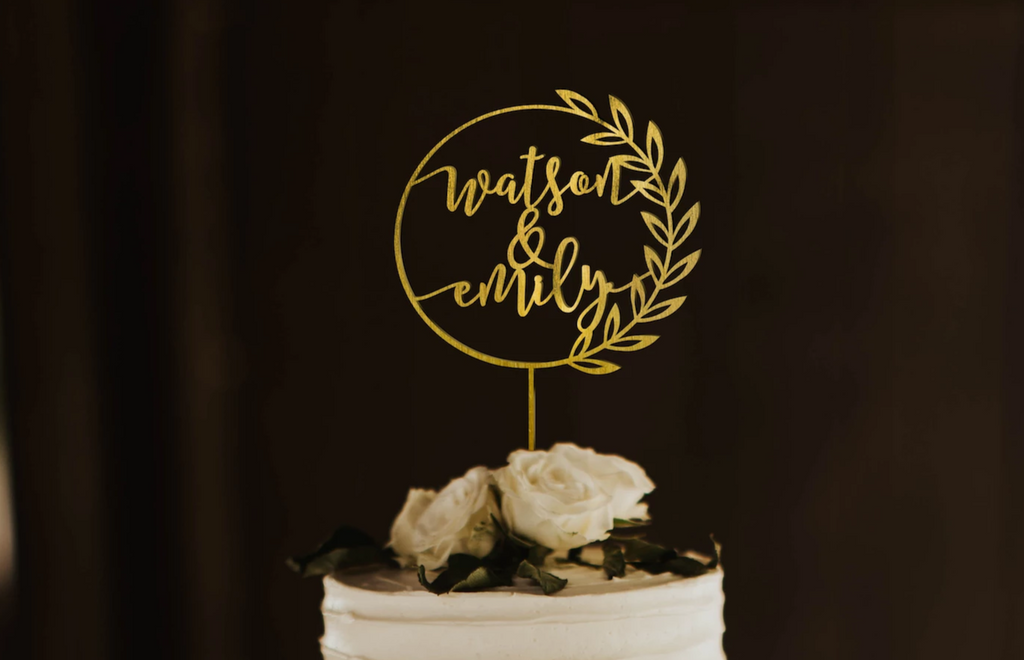 calligraphy personalized golden wreath style cake topper made of wood on top of the white simple wedding cake.