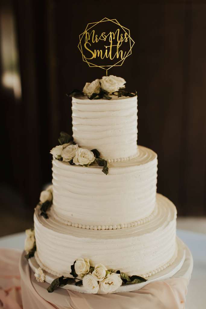 calligraphy personalized golden hexagon wreath style cake topper made of wood on top of the white simple wedding cake.