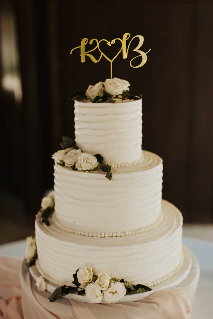 calligraphy personalized golden monogram style cake topper made of wood on top of the white simple wedding cake.