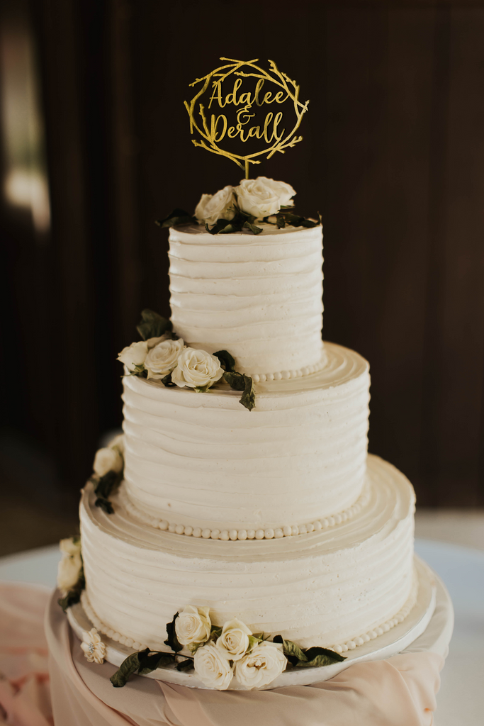 calligraphy personalized golden twig wreath style cake topper made of wood on top of the white simple wedding cake.