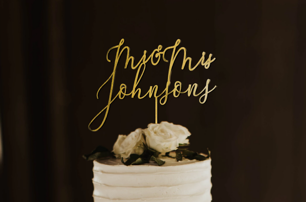 thin calligraphy personalized golden cake topper made of wood on top of the white simple wedding cake.