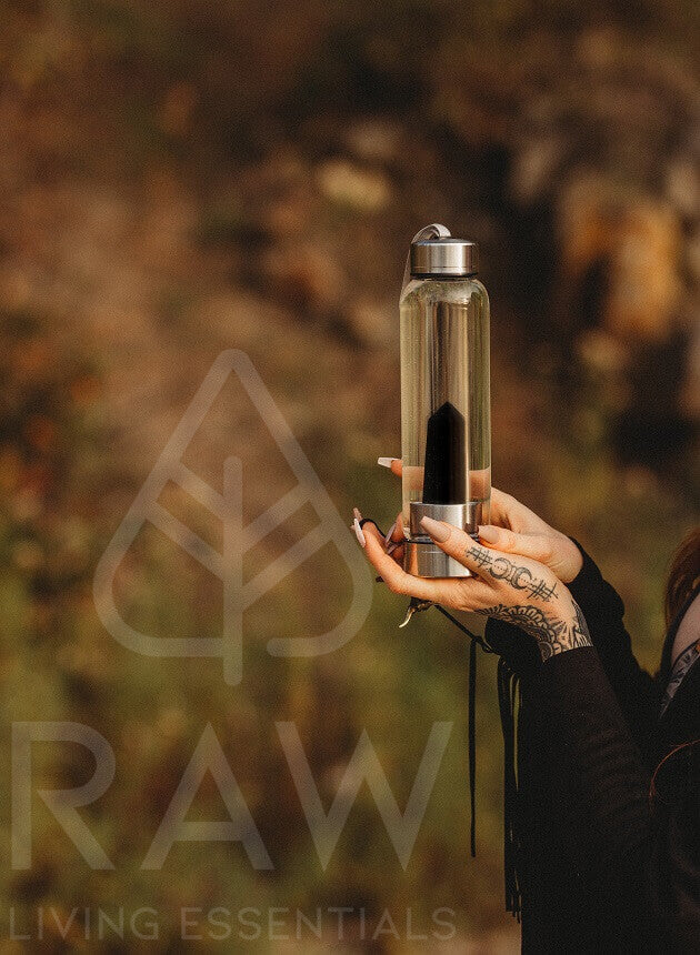 Raw Living Essentials co founder Crystal Ashley holding Obsidian Crystal Water Bottle