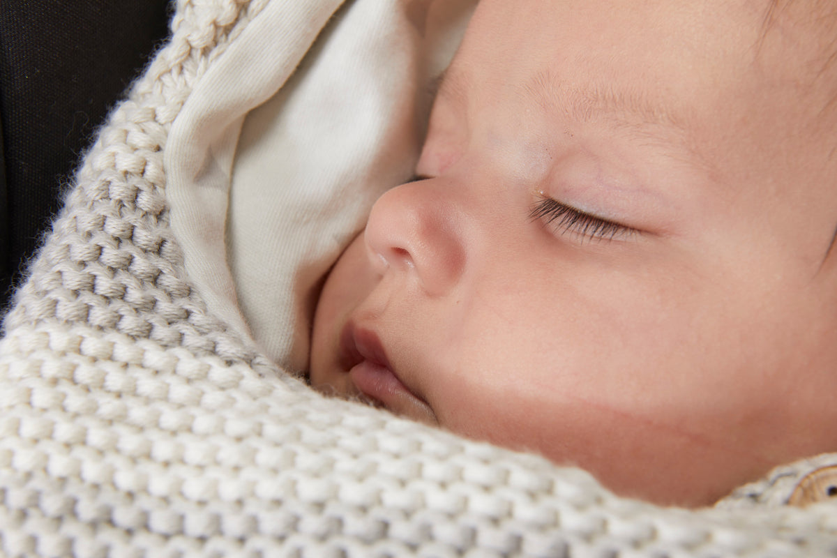 Content, sleeping baby in a car seat snuggled in a Kura Organic Baby Wrap in Pebble to keep warm.