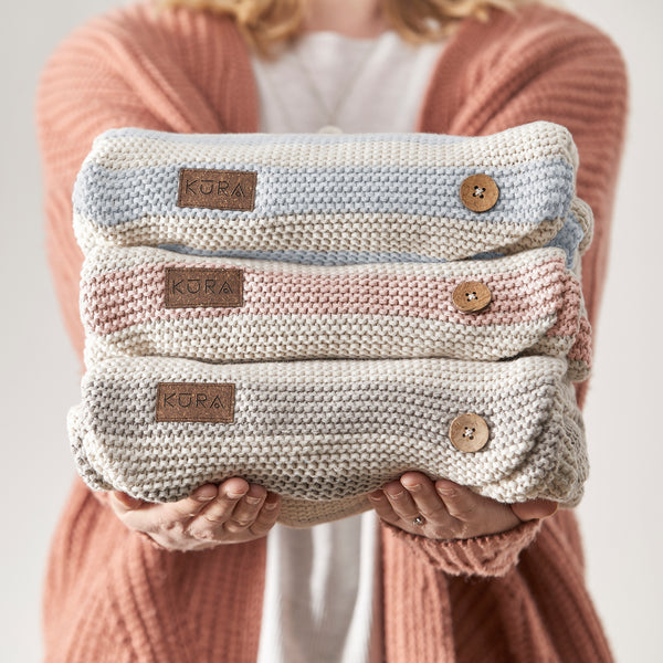 Lady holding the KURA Organics Signature Collection of Organic Baby Wraps in 3 colours - Sky, Sorbet and Pebble showing outer knit details, coconut shell buttons and recycled leather logo.