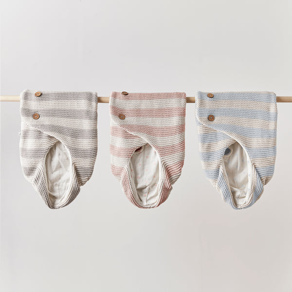 The KURA Organic Baby Wrap in Pebble, Sorbet and Sky hung over a wooden rail.