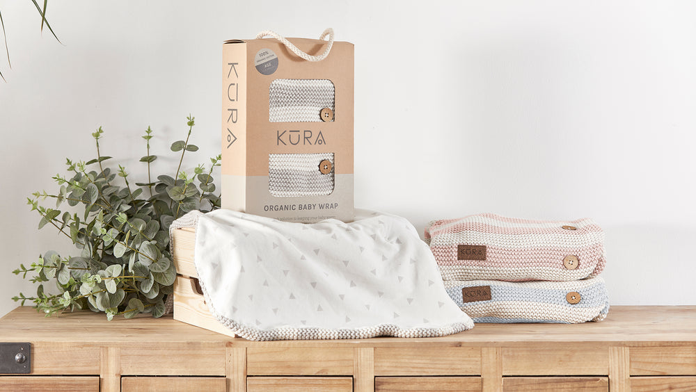 The KURA Organic Baby Wrap in Pebble packaged in an eco friendly recycled brown box with natural cotton cord handle sat on an open Organic Baby Wrap and next to 2 folded Organic Baby Wraps in Sorbet & Sky.