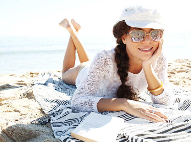 woman lying on a waterproof beach towel with sunglasses and hat