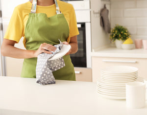 young woman wearing an apron and using a printed dishcloth to dry clean the dishes