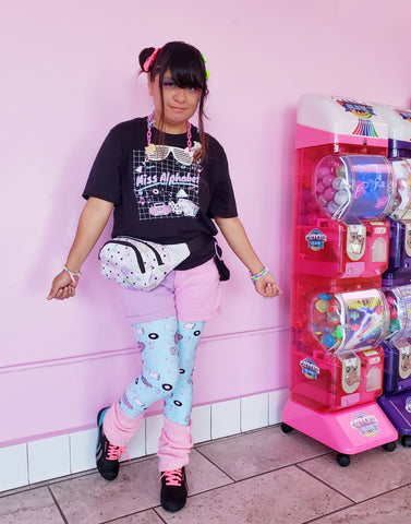woman with modeling leggings with pink boombox print, pink wall in back, next to a bubblegum machine