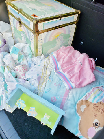 pastel colored vintage linens and unicorn trunk.
